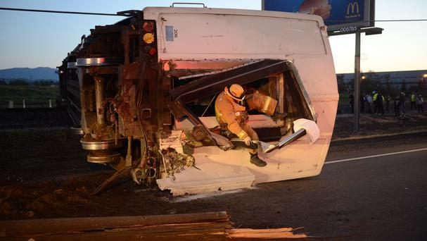 A firefighter crawls out of a passenger train car at the scene of a Metrolink accident in California. (AP)