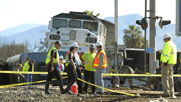 Workers stand near a Metrolink train that hit a truck and then derailed in Oxnard, California (AP)