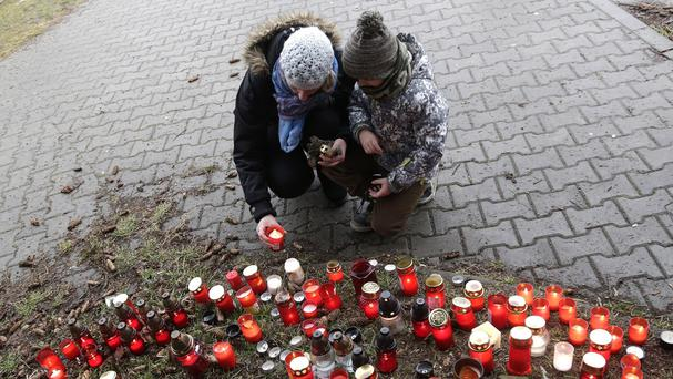 A woman with her child places a candle to pay respect to victims of the shooting in Uhersky Brod, Czech Republic (AP)