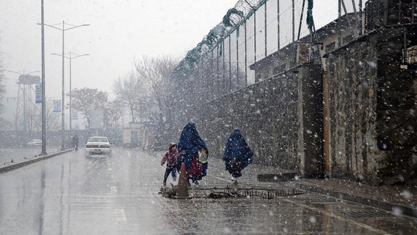Women and a child walk during a snow storm in Kabul, Afghanistan (AP)