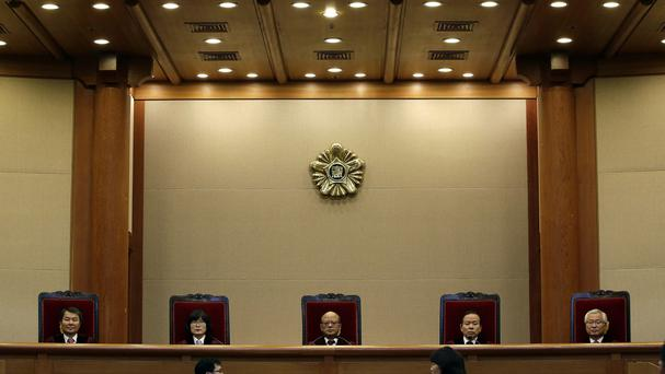 Park Han-chul, centre, president of South Korea's Constitutional Court, sits with other judges in Seoul (AP)