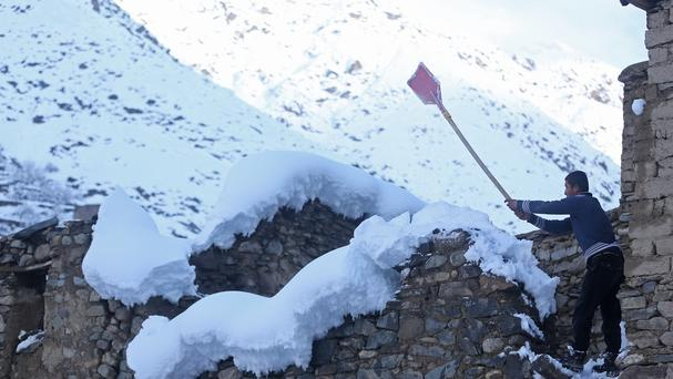 An Afghan teenager clean off the snow from his home roof top in a village close to an avalanche site in Panjshir province north of Kabul (AP)