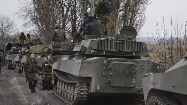 Russia-backed separatist fighters stand next to self propelled 152 mm artillery pieces in Yelenovka, near Donetsk, Ukraine (AP)