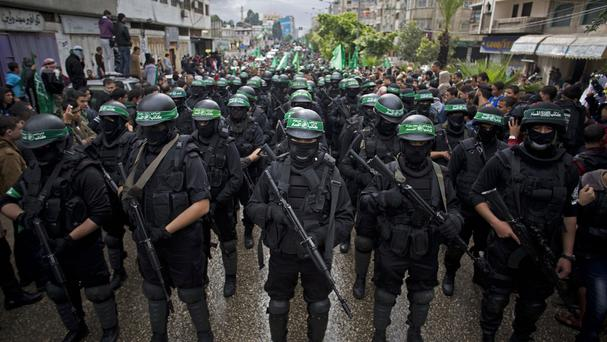 Palestinian Hamas gunmen commemorate the 27th anniversary of the group - now declared a terrorist organisation by Egypt - in Gaza (AP)
