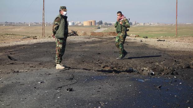 Kurdish soldiers survey the site of a bomb attack on a road between Mosul, Iraq, and the Syrian border (AP/Kurdistan Region Security Council)