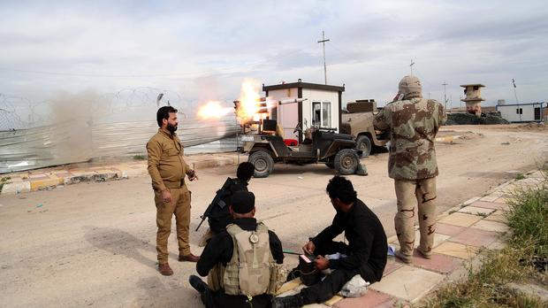 Members of an Iraqi Shia militant group called Imam Ali Brigades launch rockets against Islamic State group positions in Tikrit (AP)