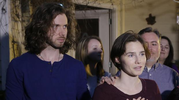 Amanda Knox, pictured with her fiance Colin Sutherland, talks to the media outside her mother's home in Seattle (AP)