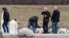 Family members pay tribute in front of a stele set up in memory of the victims in the area where the Germanwings jetliner crashed in the French Alps (AP)