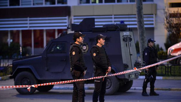 Police officers stand guard after two leftist militants attacked Istanbul Security headquarters (AP)