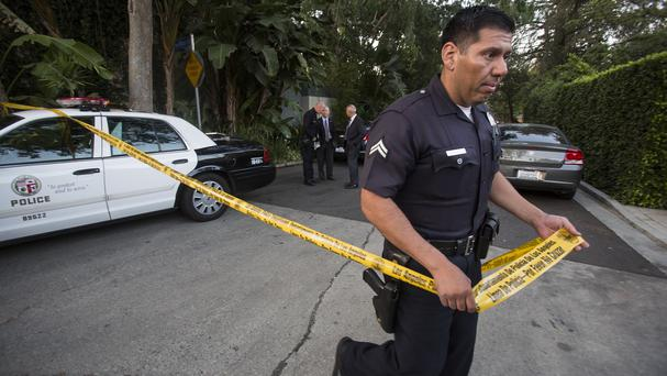 A police officer creates a perimeter outside a home in the Hollywood Hills area of Los Angeles (AP)