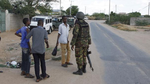 A member of Kenya Defence Forces secures the area around the Garissa University College (AP)