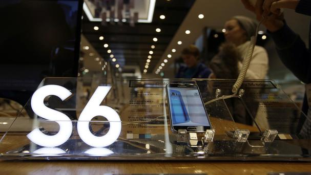 Visitors look at Samsung's new smartphone the Galaxy S6 as the technology giant announced its quarterly operating earnings fell 31 per cent from a year earlier (AP)