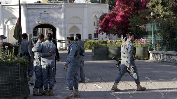 Policemen console each other at the site of a deadly attack by an Afghan national army soldier in the compound of the provincial governor in Jalalabad (AP)
