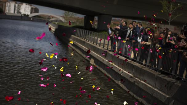 Members of Spain's gypsy community throw flower petals into the Manzanares river during an event in memory of the Roma victims of the Nazi Holocaust in Madrid (AP)