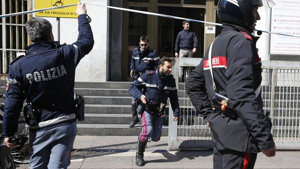 Policemen run out of the tribunal building in Milan (AP)