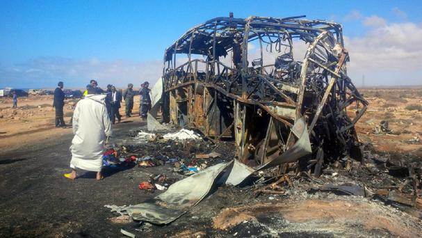 Emergency workers and officials inspect the burnt-out remains of a road accident between a truck and a bus near the southern city of Tan-Tan, Morocco (AP)