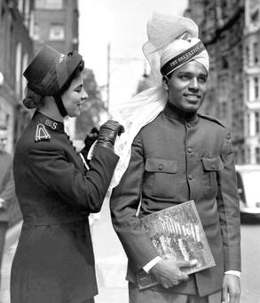 SOLDIERS OF THE LORD: Eva Burrows straightening the puggaree worn by a fellow delegate at the Salvation Army's first international youth congress in London in 1950. Photo: AP