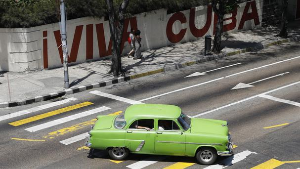 A taxi driver steers his classic American car through Havana (AP)