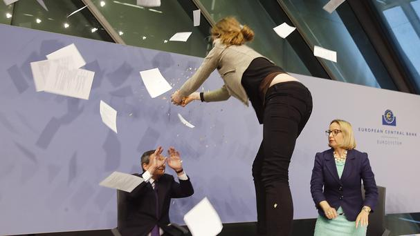 An activist throws paper at European Central Bank president Mario Draghi during a press conference (AP)