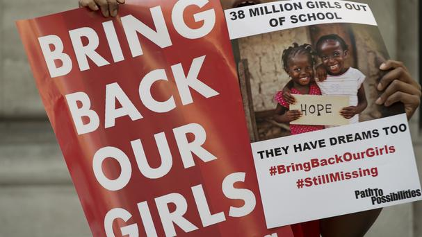 Protesters holds up placards demanding help from the Nigerian government to find the 219 girls who remain missing (AP)