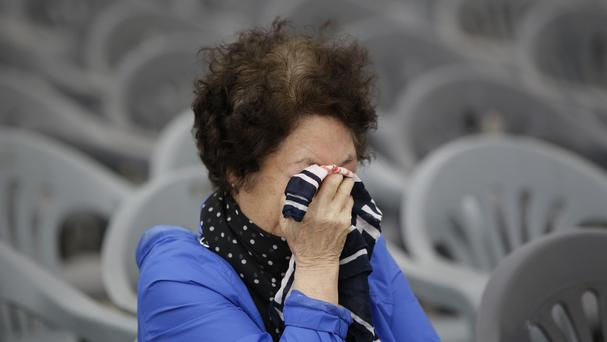 A woman wipes her tears outside a group memorial altar for the victims of the sunken ferry Sewol, in Ansan (AP)