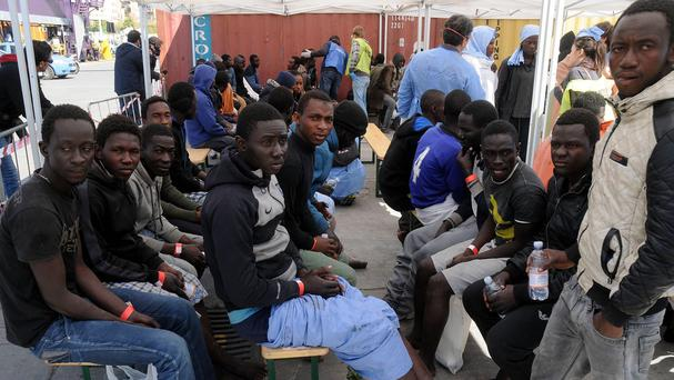 Migrants rest upon disembarking at Palermo's harbour after being rescued at sea (AP)