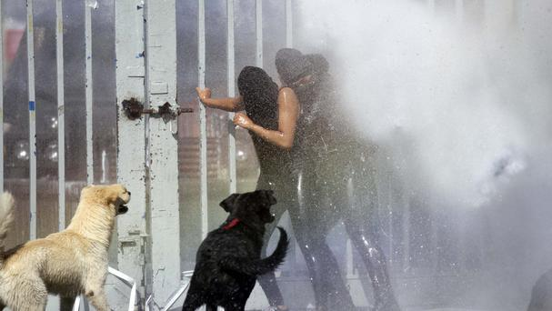 Protesters are drenched with water from a police water cannon during clashes in the courtyard of the University of Santiago (AP)