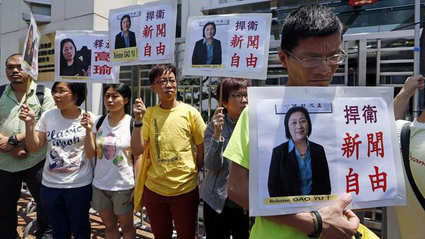 Anti-Beijing protesters hold pictures of jailed veteran Chinese journalist Gao Yu during a rally outside Chinese central government's liaison office in Hong Kong (AP)