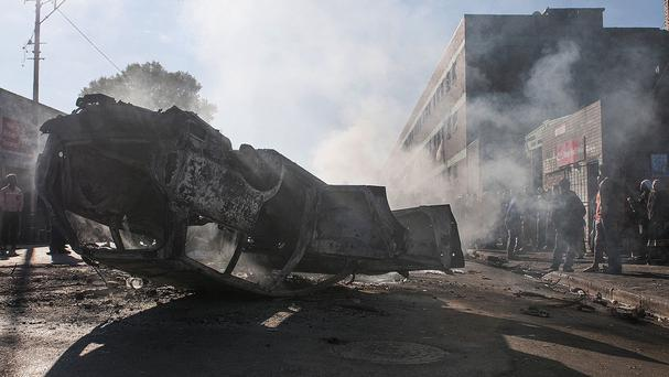 People gather round burned out vehicles in Johannesburg (AP)