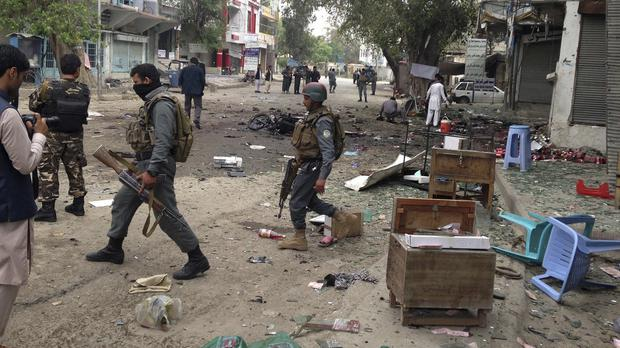 Afghan security forces inspect the site of a suicide attack near a bank in Jalalabad, east of Kabul (AP)