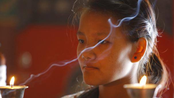 Sumi Sherpa lights a lamp in memory of those killed on Everest a year ago (AP)