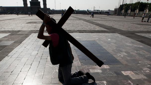 A migrant bears a cross while walking on his knees to the entrance of the Basilica of Guadalupe, in Mexico City (AP)