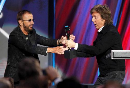 Ringo Starr reaches for his award after being inducted by Paul McCartney to the Rock and Roll Hall of Fame at an event in Cleveland