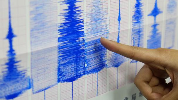 An employee of the Taiwan Central Weather Bureau points at a seismic chart showing the moment of a 6.3 magnitude earthquake (AP)