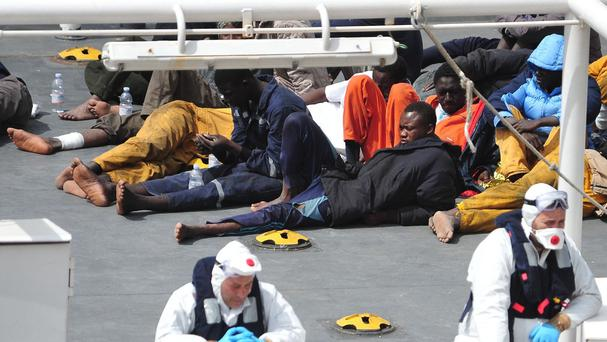 Survivors of the smuggler's boat that overturned off the coasts of Libya on the deck of an Italian Coast Guard ship. (AP)