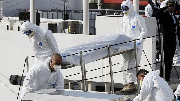Italian coastguard officers carry the body of a migrant off the ship Bruno Gregoretti, in Valletta, Malta (AP)