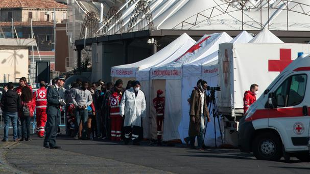 Migrants wait to enter a Red Cross tent after disembarking from the Italian Finance Police vessel Denaro in the harbor of Catania, Sicily, southern Italy (AP)