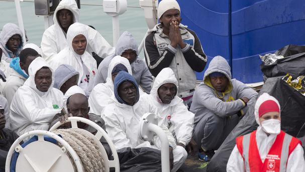 Migrants wait to disembark from an Italian coastguard ship in Sicily. (AP)