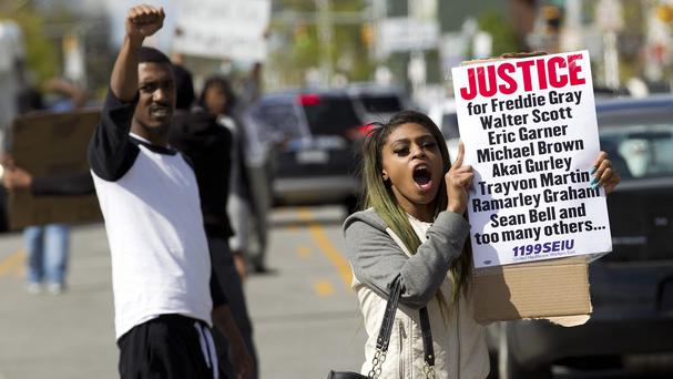Caira Byrd holds a placard supporting Freddie Gray outside Vaughn Greene Funeral Home during his wake in Baltimore (AP)