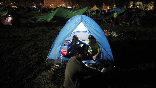 A Nepalese man eats food inside a tent as people stay on open ground over fears of earthquake tremors in Kathmandu (AP)
