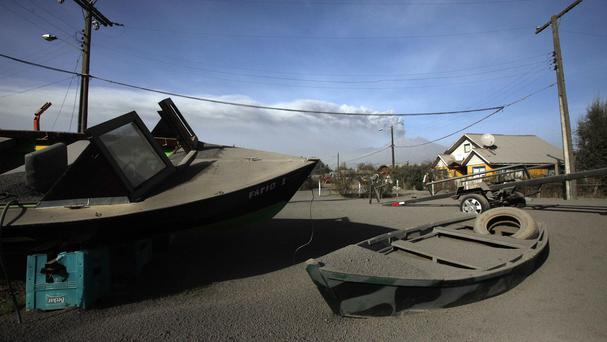 Boats dusted with volcanic ash deposited from the eruptions of the nearby Calbuco volcano in Puerto Varas, Chile (AP)