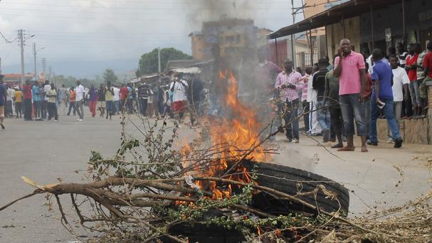 Residents gather around a burning tyre roadblock following clashes between police and opposition protesters in a street in Bujumbura, Burundi (AP)