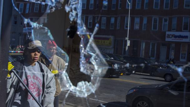 Residents, reflected off broken glass, clean up after an evening of riots following the funeral of Freddie Gray in Baltimore (AP)