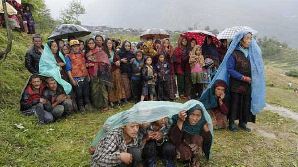 Villagers wait in the rain as an aid relief helicopter lands at their remote mountain village of Gumda, near the epicentre of Saturday's massive earthquake in the Gorkha District of Nepal (AP)