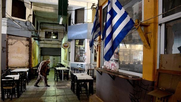 A man walks past a Greek flag in the central market of the northern port city of Thessaloniki (AP)