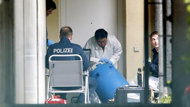German police officers secure evidence in front of an apartment in Oberursel (AP)