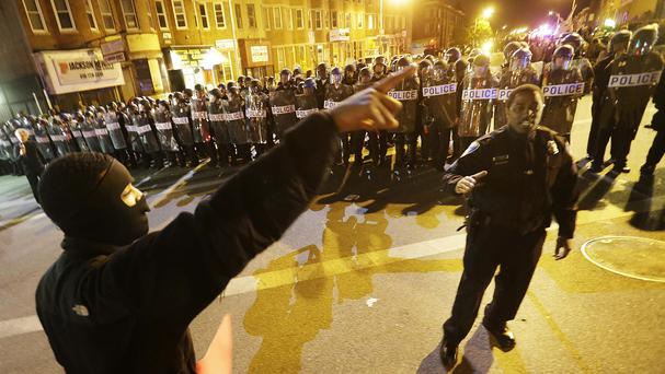 A protester argues with a policeman amid demonstrations in Baltimore (AP)