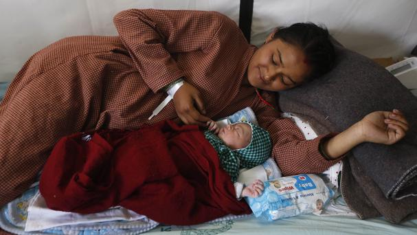 Nepalese woman Lata Chand,19, looks at her newly born baby girl at the Israeli field hospital in Kathmandu (AP)