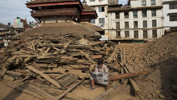 A man reads a newspaper at Basantapur Durbar Square, damaged in the April 25 earthquake in Kathmandu, Nepal (AP Photo/Bernat Amangue)
