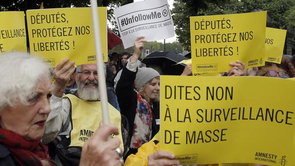 Demonstrators hold placards during a protest in Paris against a new government surveillance law (AP)